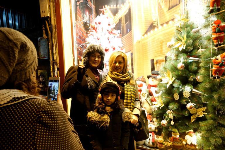 Des Iraniennes se font prendre en photo devant une vitrine de décorations de Noël dans des boutiques de Téhéran, le 24 décembre 2016.
